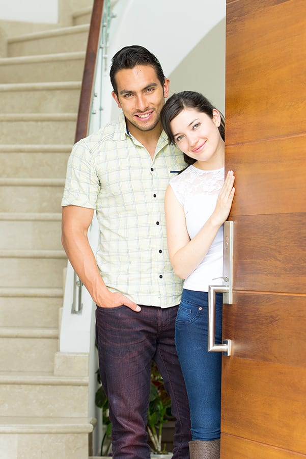 happy attractive loving couple opening the door to their new house